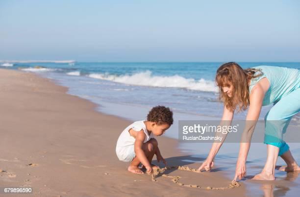 Grandma and her granddaughter drawing on sea sand.