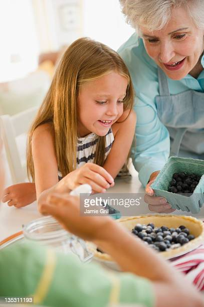 Grandma baking blueberry pie with grandchildren