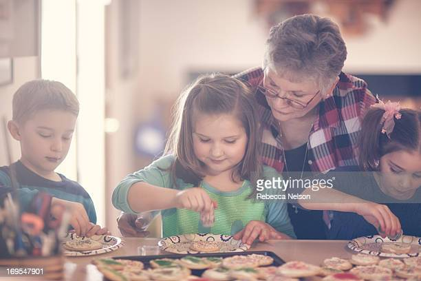 Grandma decorating cookies with her grandchildren