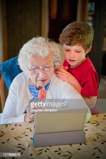 grandma & grandson exploring her tablet computer : Stock Photo