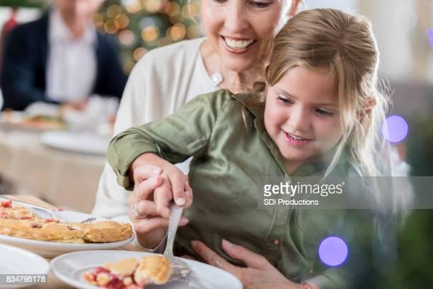 Grand-mère aide pie servir petite-fille après le dîner de Noël