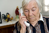 Female senior gets a sad message transmitted on the telephone