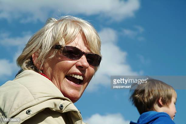 Grandma laughing with grandson against blue sky