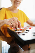 Old woman playing checkers board game in retirement home, thinking about her next move. The senior lady smiles while holding draughts