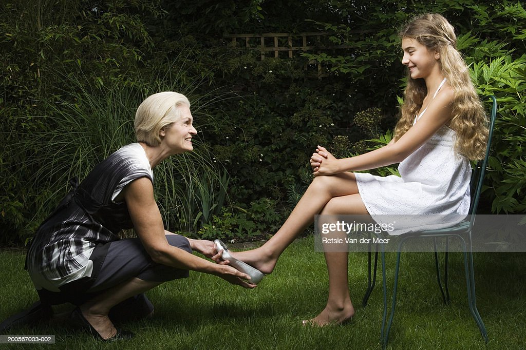Grandma putting silver shoe on granddaughter's (10-11) foot in garden