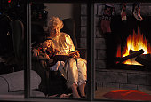 Grandma Reading Story To Grandson Next To Fireplace