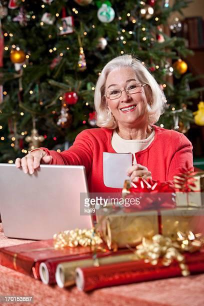 Grandma de compras en línea con el ordenador portátil para Navidad regalos