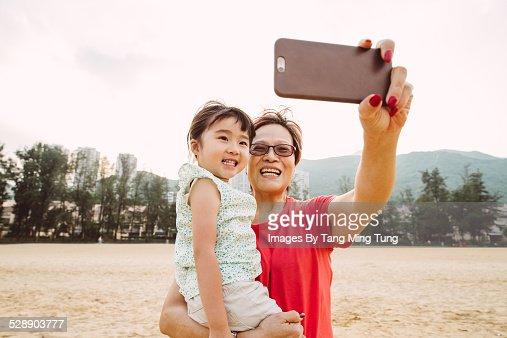 Grandma taking selfies with toddler on beach