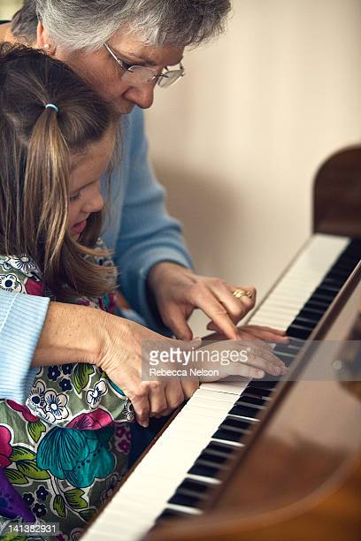 Grandma teaching granddaughter how to play piano