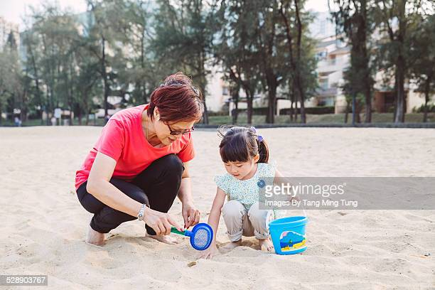 Grandma & toddler playing sand joyfully on beach