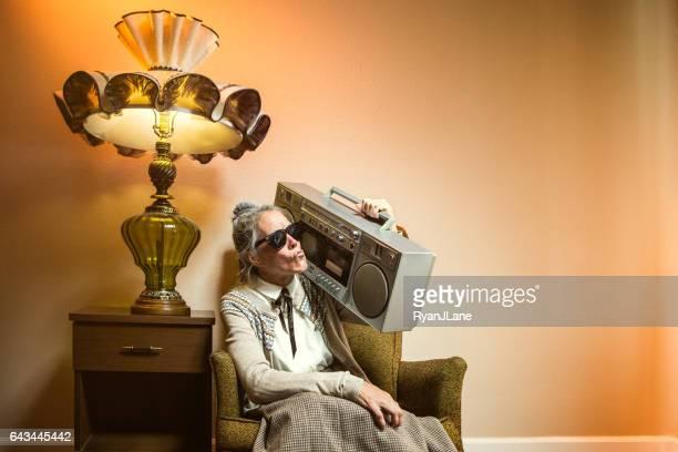 Grand-mère à l'aide de divers appareils électroniques modernes