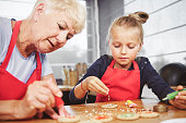 Grandma with girl applying icing on cookies