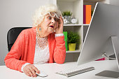 Grandma working at the office and looking at the computer in disbelief lifting her glasses up