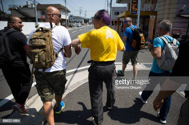 Grandmaster Masaaki Hatsumi center walks with his highranked disciples after a lesson outside the Bujinkan dojo on May 21 2017 in Noda Japan The...