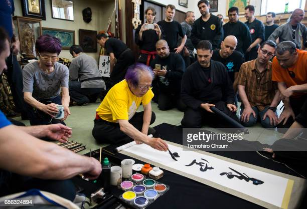 Grandmaster Masaaki Hatsumi writes calligraphy for a highlanked disciple after a lesson at the Bujinkan dojo on May 21 2017 in Noda Japan The...