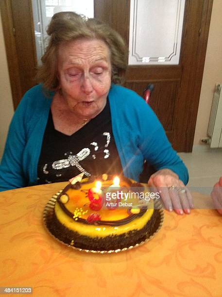 Grandmother 90's birthday celebration at home with candles and numbers on the cake