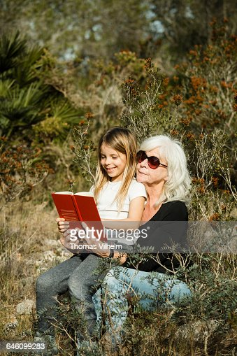Grandmother and child reading in the woods