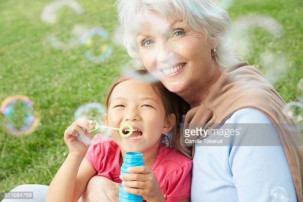 Grandmother and grandaughter playing with bubbles