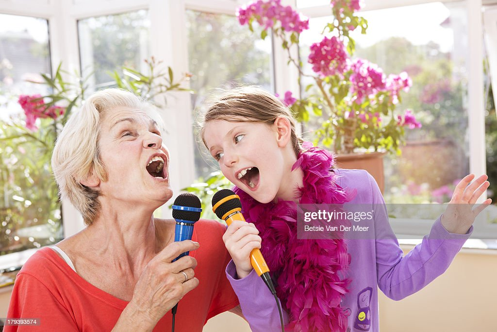 Grandmother and grandchild singing karaoke. : Stock Photo