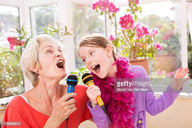 Grandmother and grandchild singing karaoke.