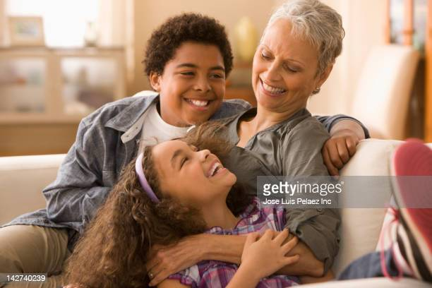 Grandmother and grandchildren laughing on sofa
