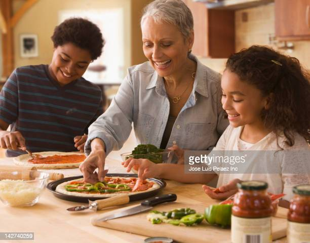 Grandmother and grandchildren making pizza