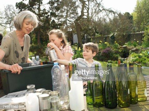 Grandmother and grandchildren (6-10) recycling bottles in garden