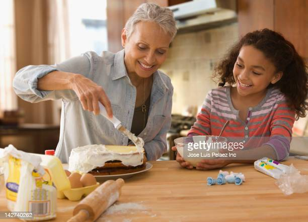 Grandmother and granddaughter baking a cake