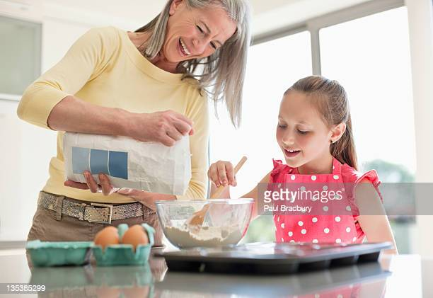 Grandmother and granddaughter baking cupcakes together