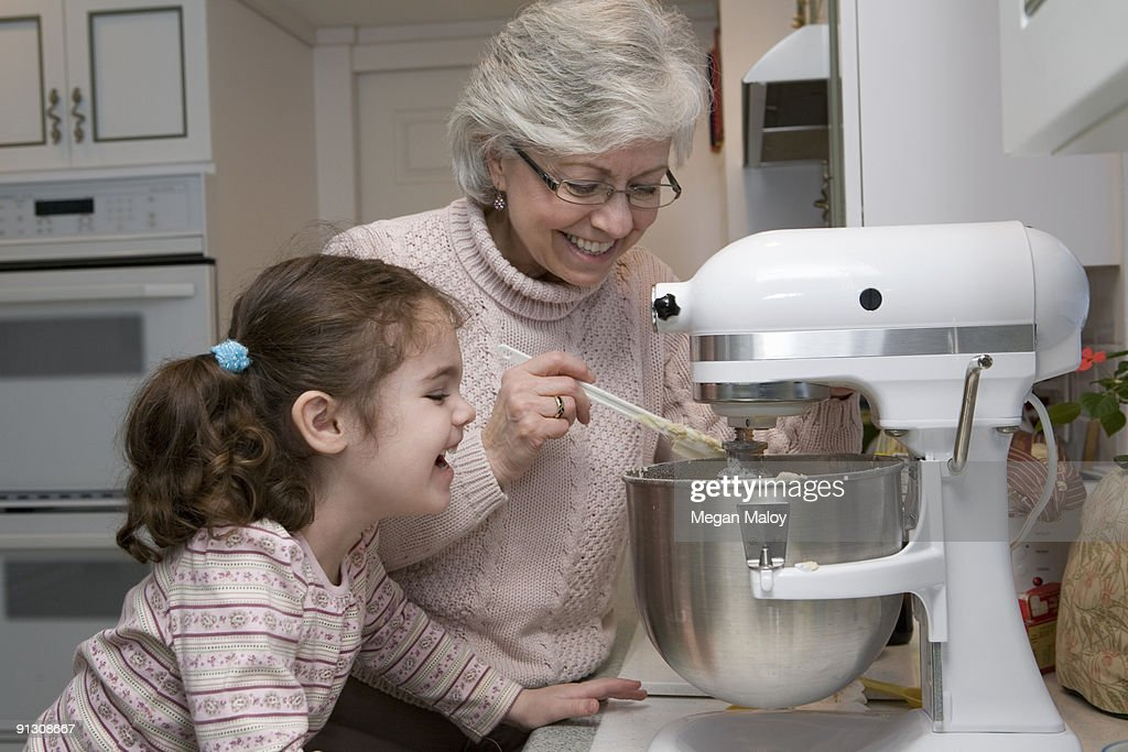Grandmother and granddaughter baking together. : Stock Photo