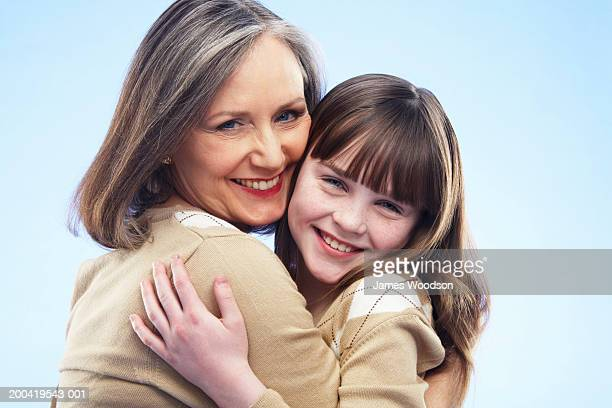 Grandmother and granddaughter (8-10) embracing, portrait, close-up