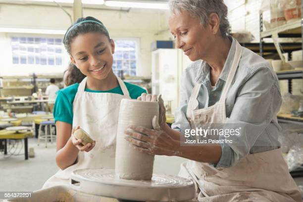 Grandmother and granddaughter forming pottery on wheel in studio