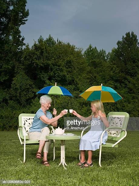Grandmother and granddaughter (8-9) having tea party in backyard