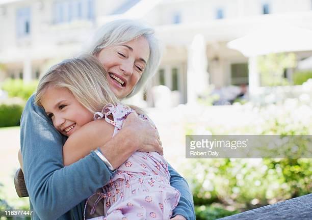 Grandmother and granddaughter hugging in backyard