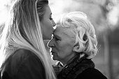 Kiss! Cute girl kissing her granny. Profile. Black and white.