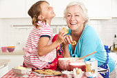 Grandmother And Granddaughter Baking In Kitchen Smiling And Laughing.