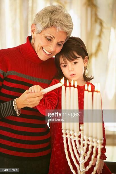 Grandmother and granddaughter lighting menorah candles
