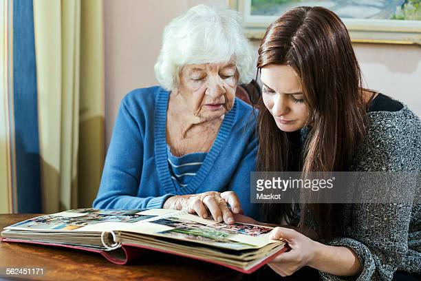 Grandmother and granddaughter looking at photo album in house