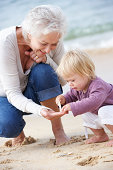 Grandmother And Granddaughter Looking at Shell On Beach Together Smiling