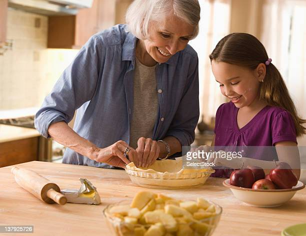 Grandmother and granddaughter making pie crusts