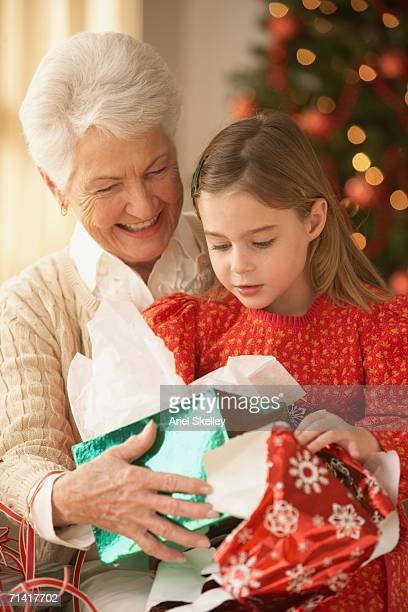 Grandmother and granddaughter opening Christmas presents