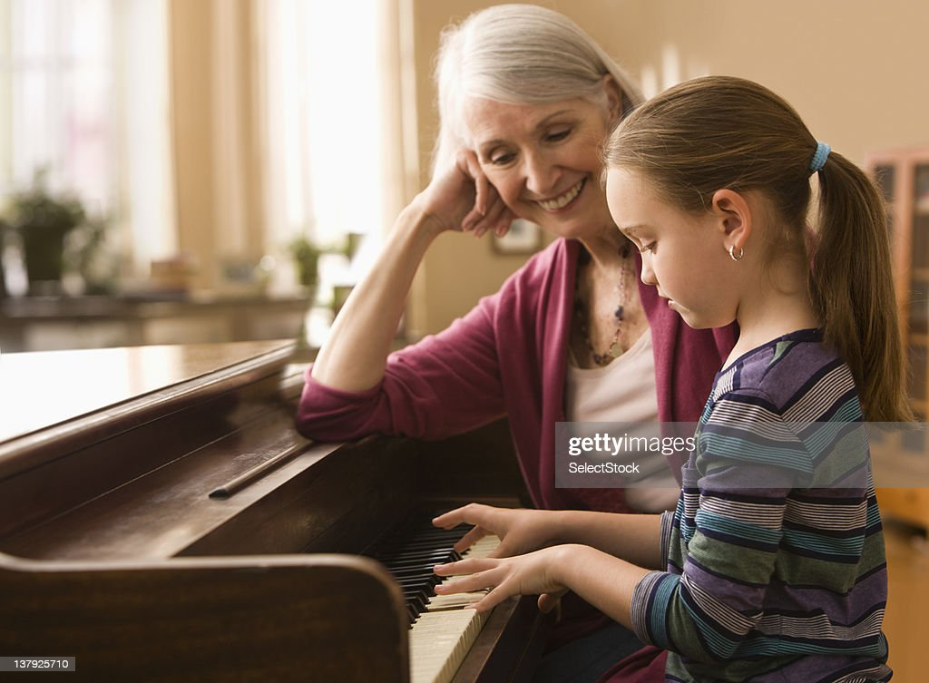 Grandmother and granddaughter  play piano : Stock Photo