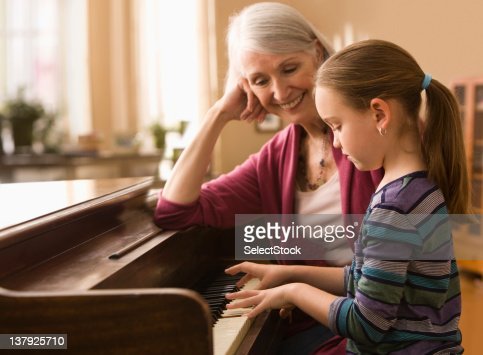 Grandmother and granddaughter  play piano