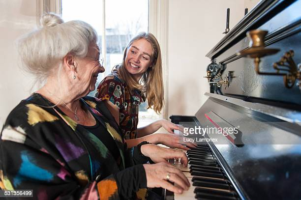 Grandmother and granddaughter playing the piano
