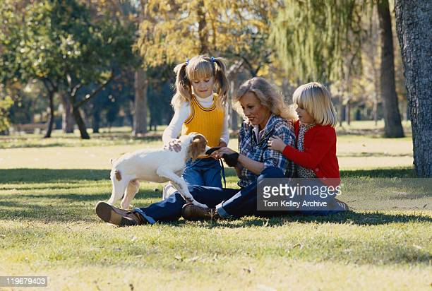 Grandmother and granddaughter playing with dog on grass