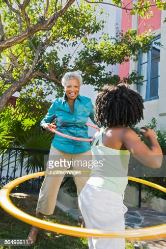 Grandmother and granddaughter playing with plastic hoops