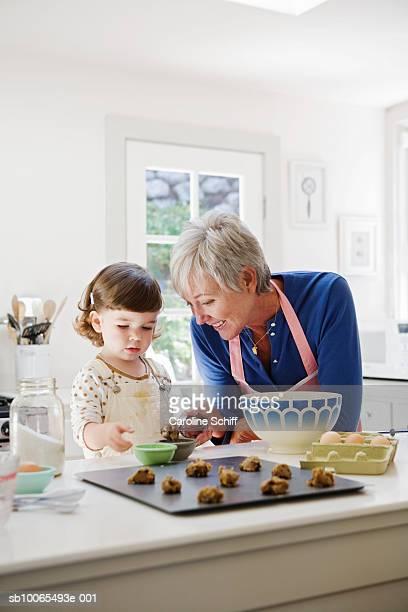 Grandmother and granddaughter (2-3) preparing cookies in kitchen