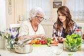 Grandmother and granddaughter preparing food together at kitchen.