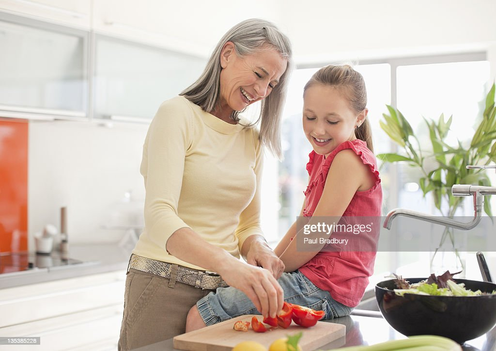 Grandmother and granddaughter preparing food together : Stock Photo