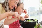 Grandmother and granddaughter preparing salad
